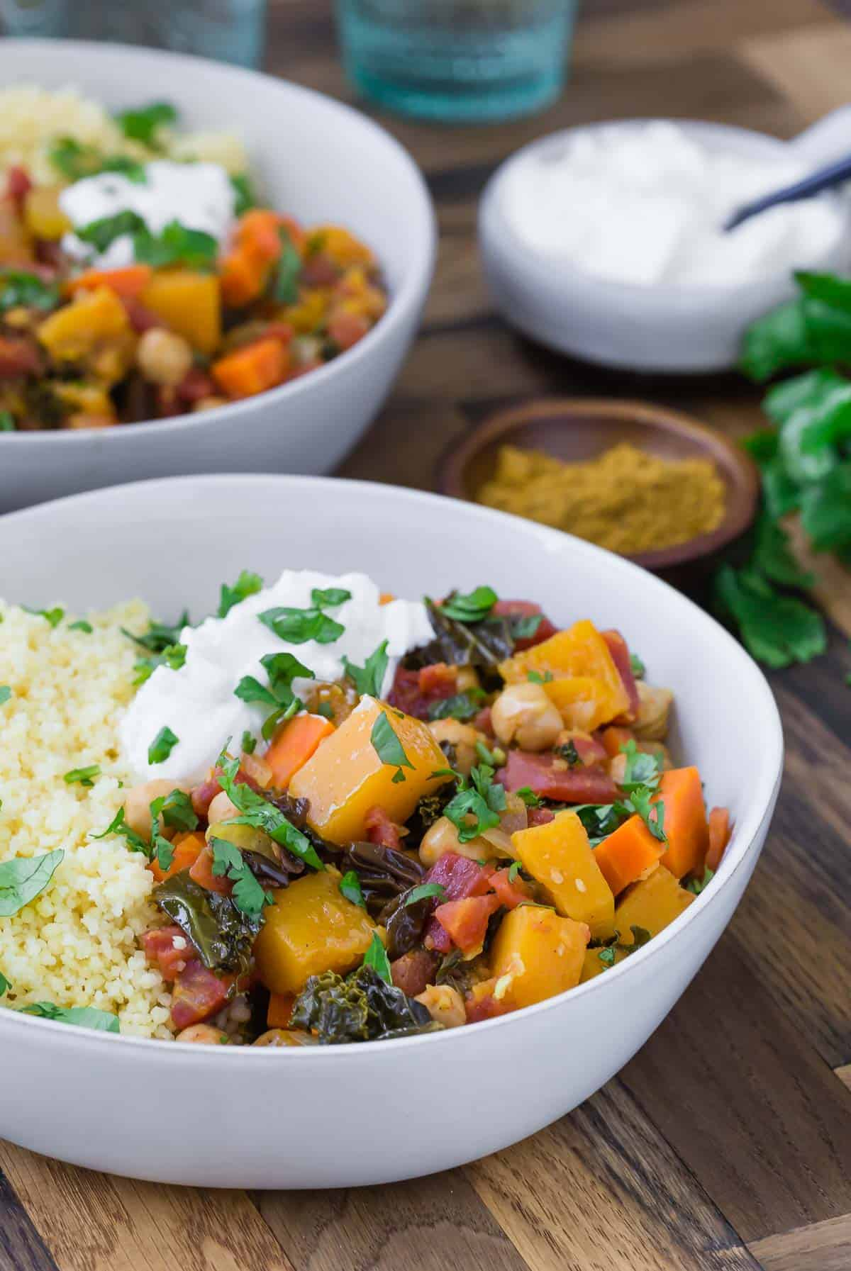 Two large white bowls with vegetarian moroccan squash stew with a small bowl of yogurt and fresh cilantro also pictured.