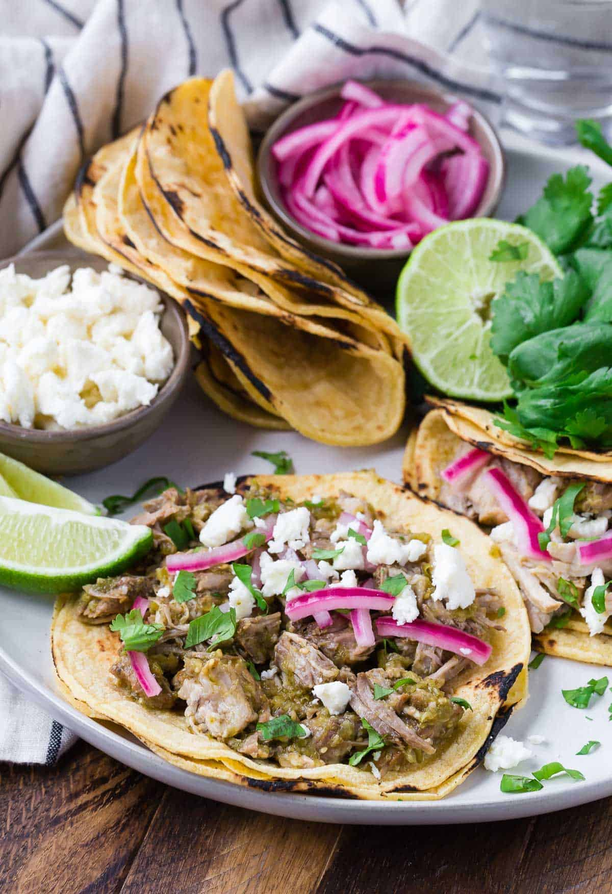 Pork verde tacos on a round platter with toppings and additional tortillas.