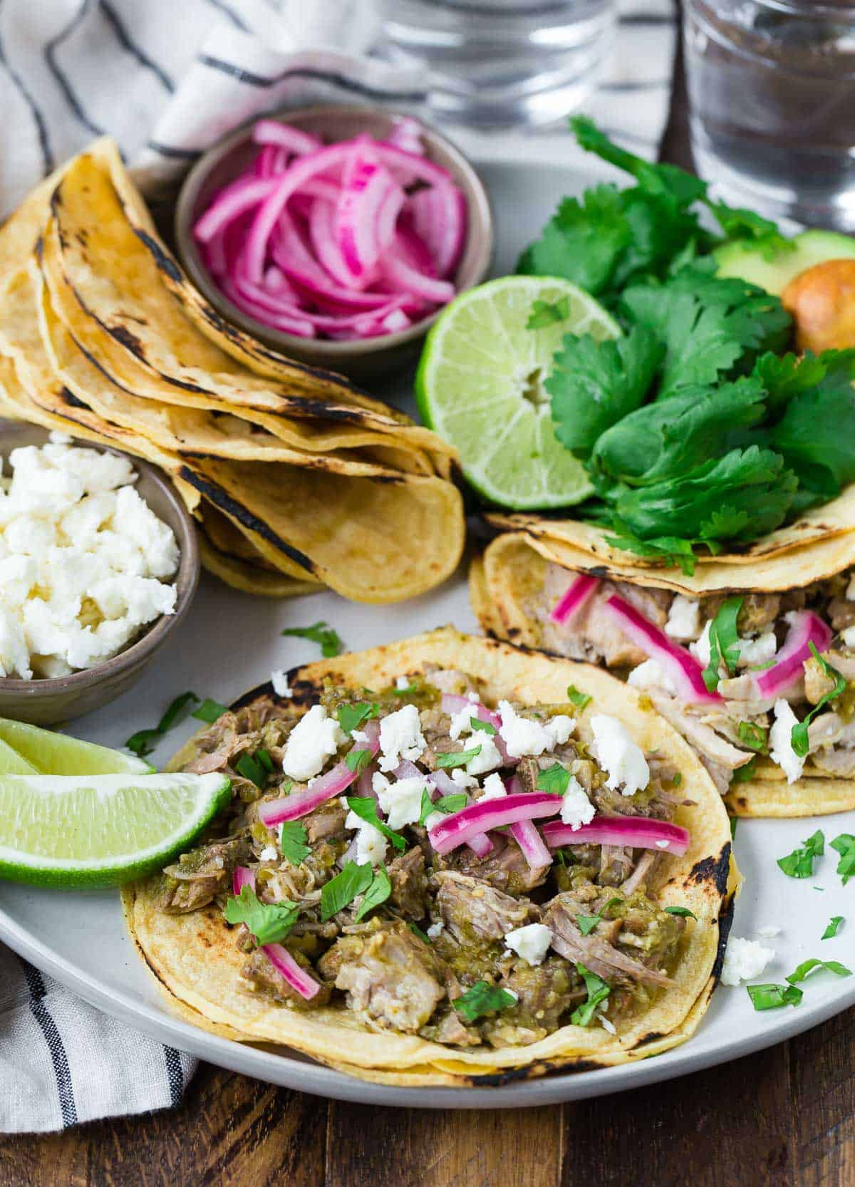 Amazing slow cooker pork tacos on a plate with assorted toppings.