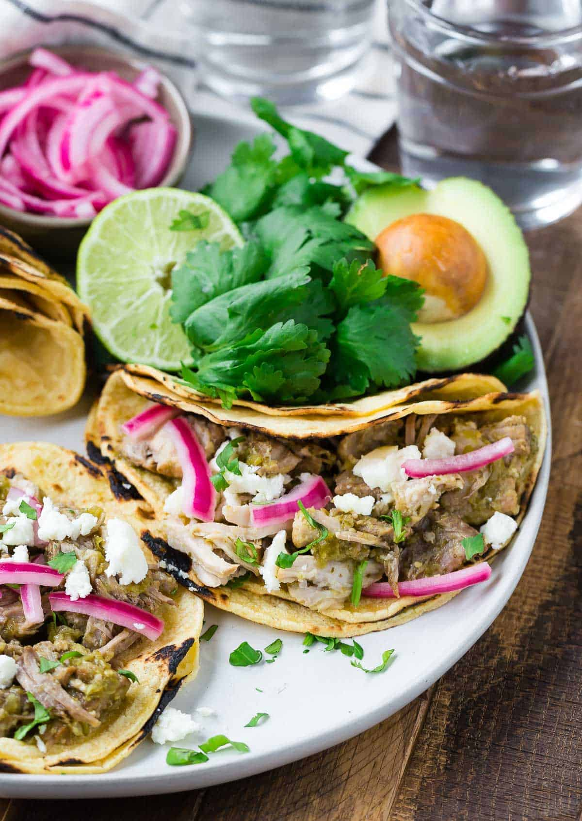 Pork tacos on a plate with cilantro, avocados, and pickled red onions.