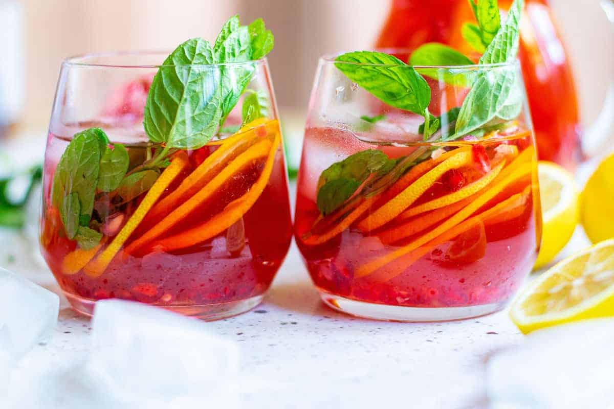 Two stemless glasses of bright red sparkling punch with citrus slices and mint leaves.