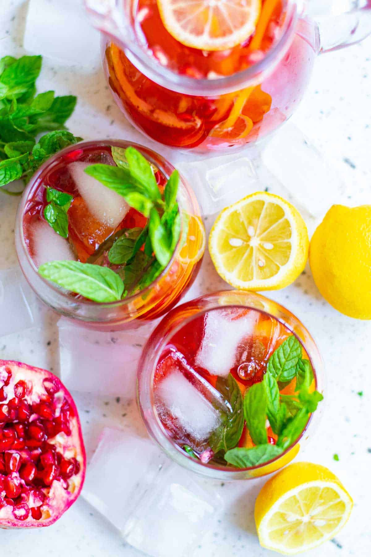 Overhead view of two glasses of sparkling pomegranate punch, garnished with fresh pomegranate and mint leaves.