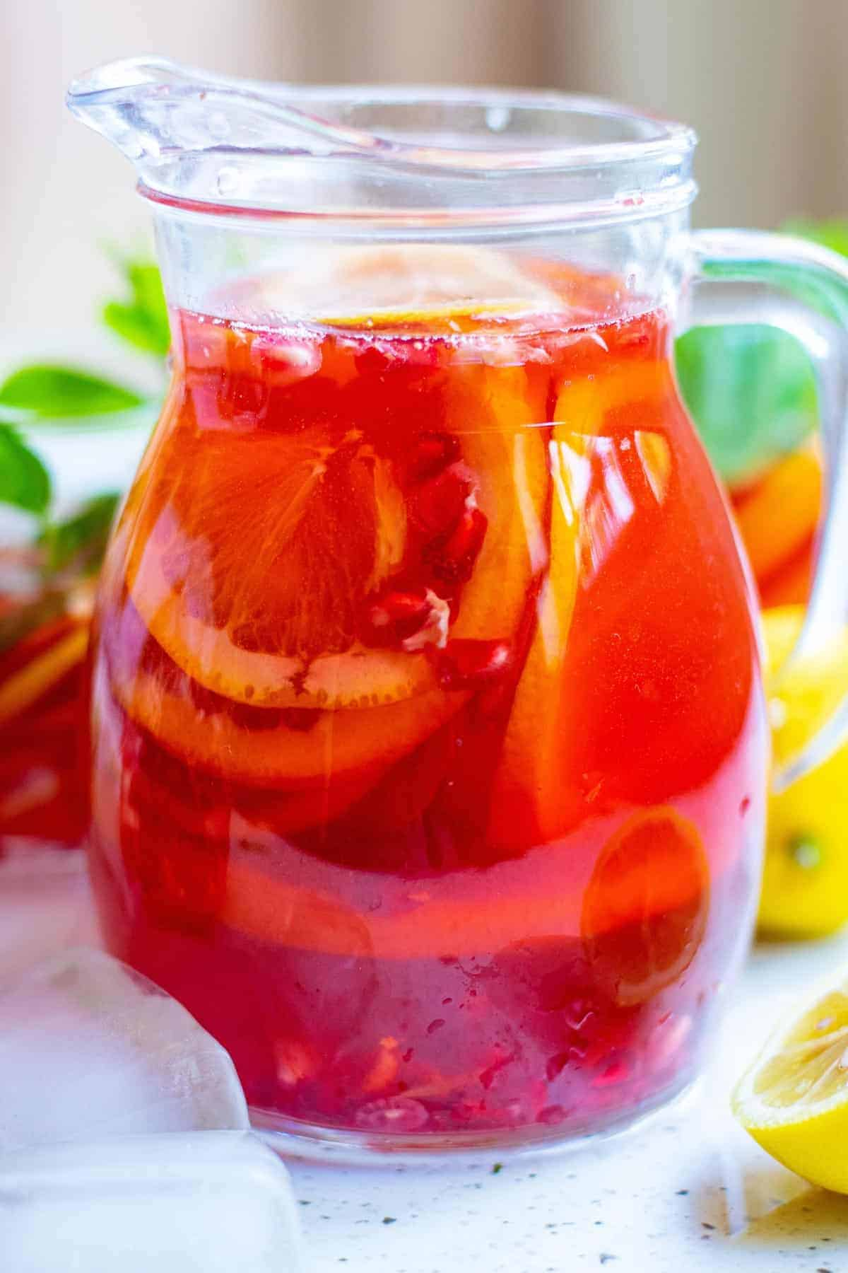Pitcher of bright red punch with citrus slices.