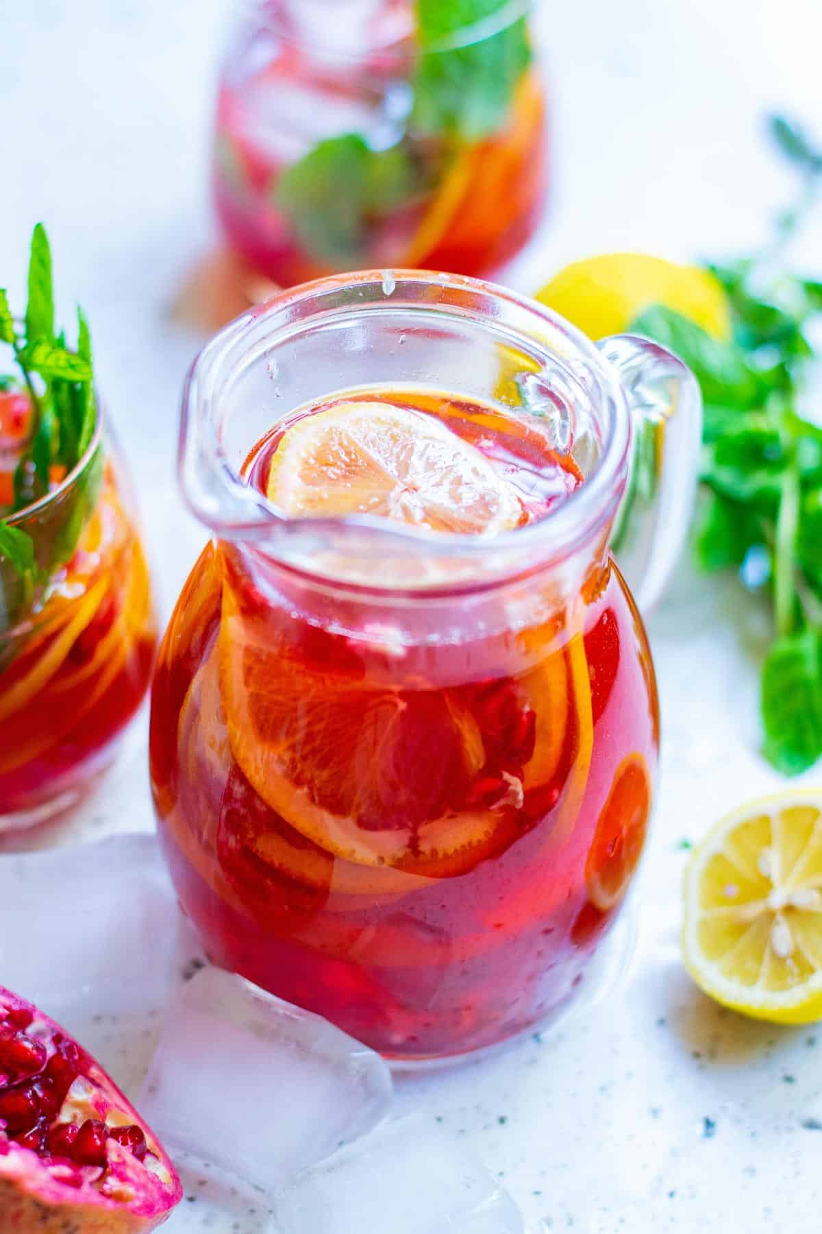 Pitcher of red punch with colorful fresh garnishes.