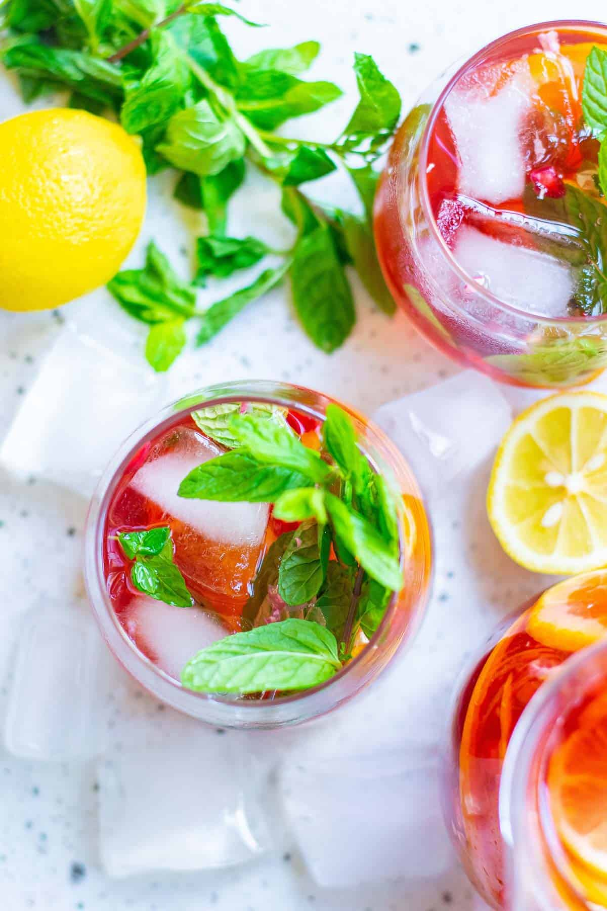 Overhead view of a glass of bright red punch with mint leaves.
