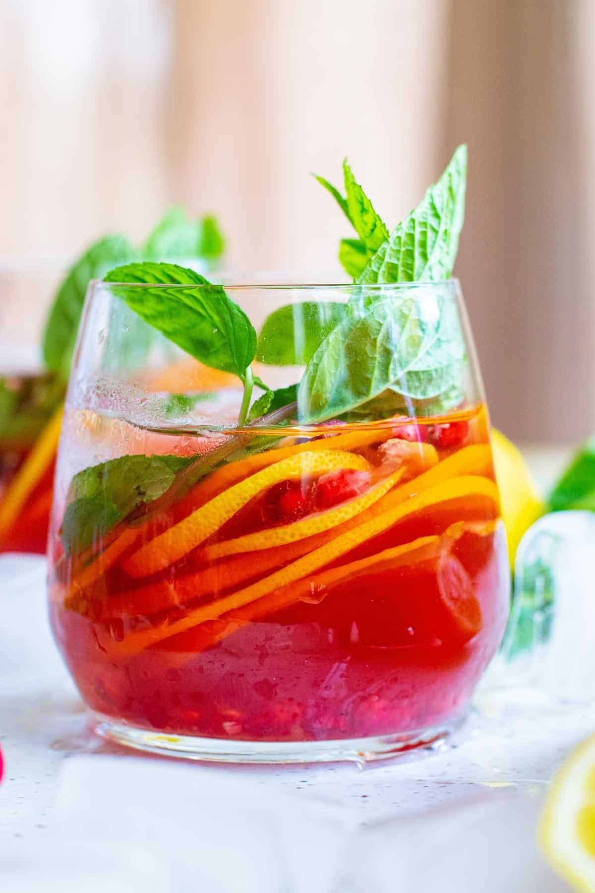 Close up view of stemless glass with bright red drink with pomegranate arils, citrus slices, and fresh mint leaves.