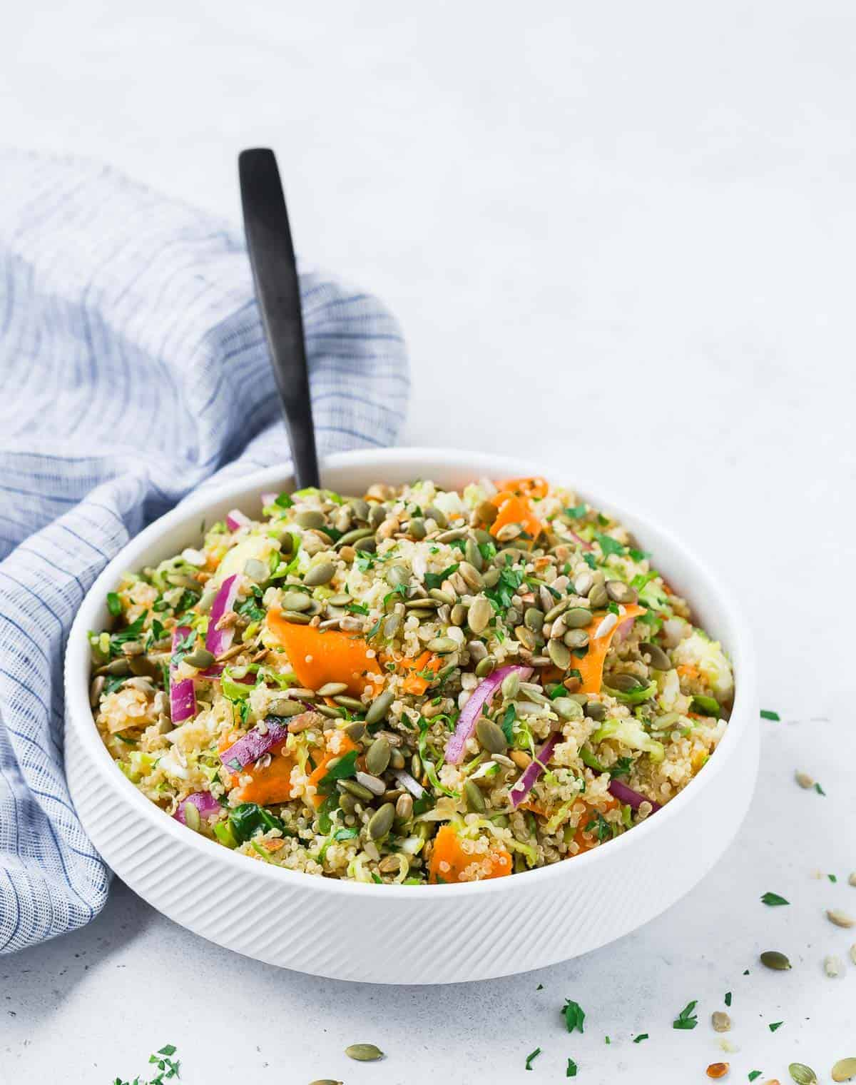 A white bowl filled with colorful salad with quinoa, brussels sprouts, carrots, and red onions.