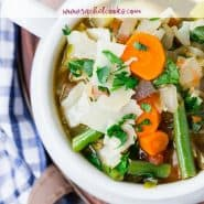 """Colorful soup in a white bowl, text overlay reads """"amazingly healthy vegetable soup, rachelcooks.com"""""""