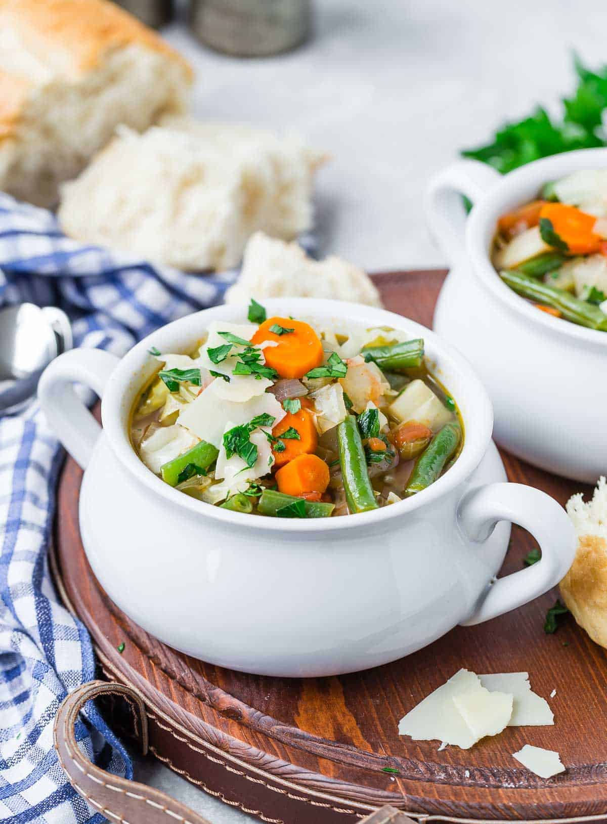 Bowl of soup with vegetables in a small crock style bowl, bread in background.