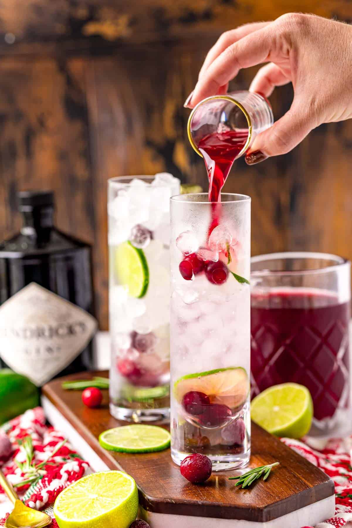 Cranberry being poured into a G&T cocktail.