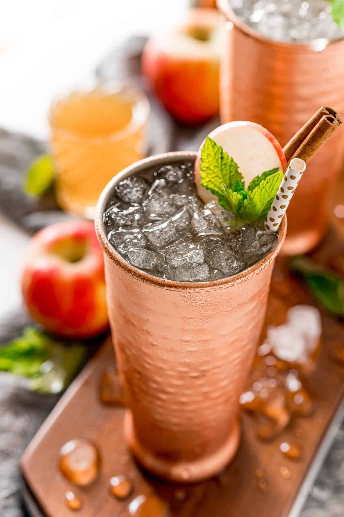 Apple cider moscow mule with nugget ice, garnished with apple, mint leaves, and a cinnamon stick.