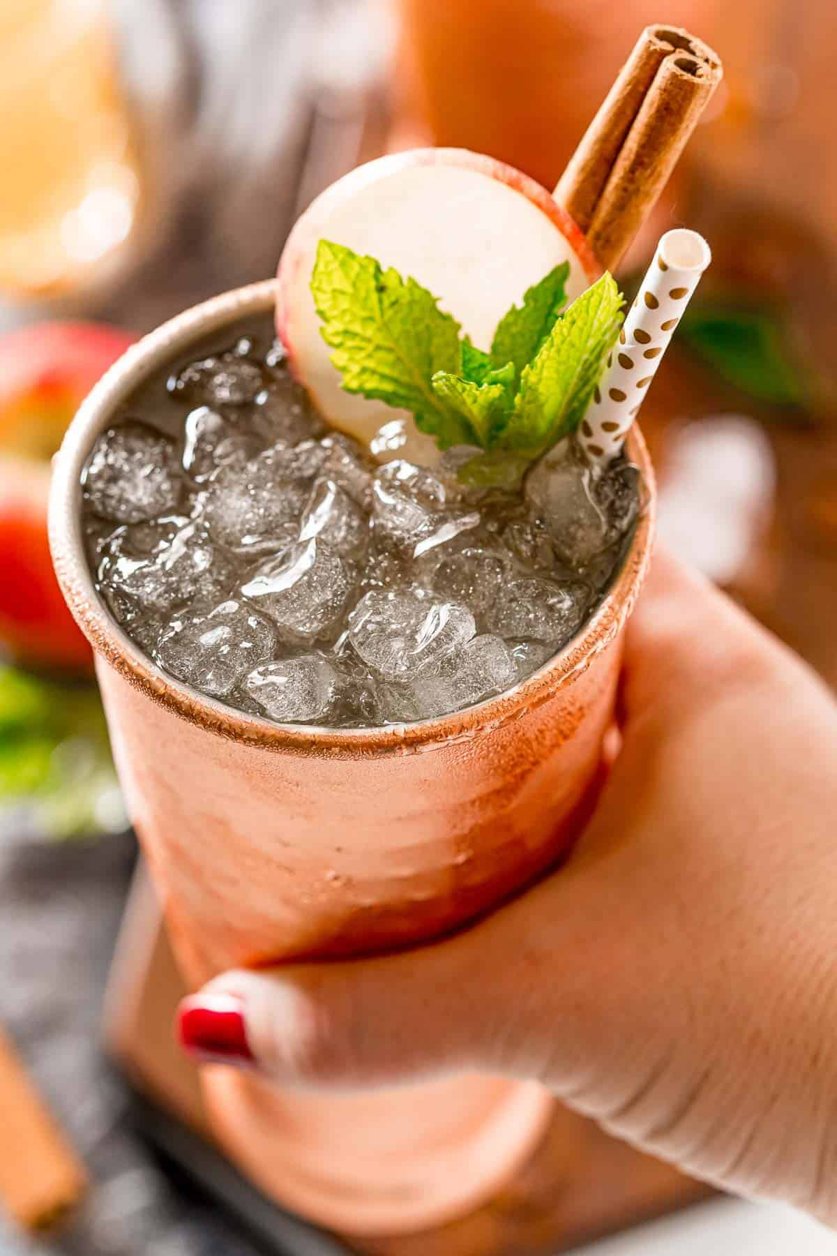 Apple cider moscow mule in a woman's hand.