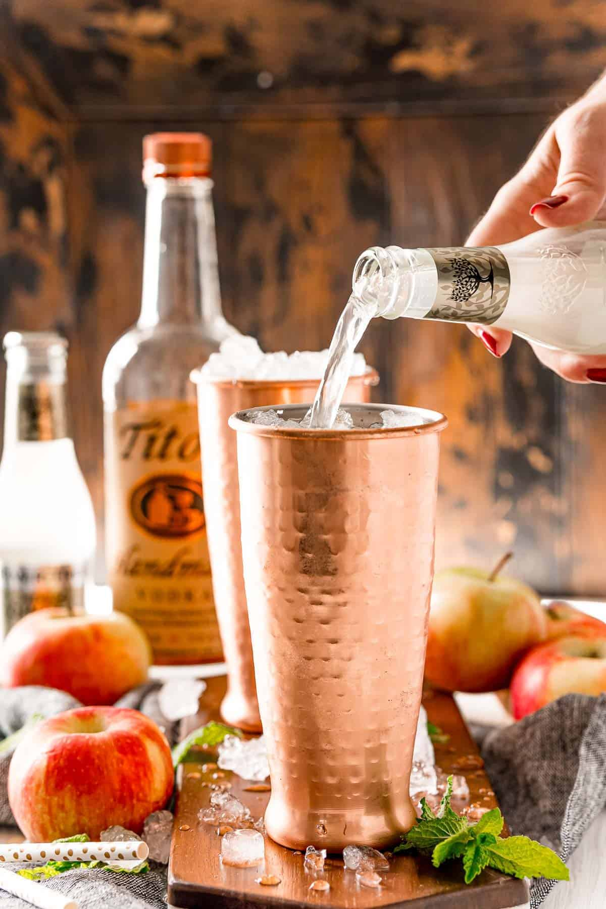 Ginger beer being poured into a copper mug.