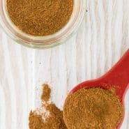 Apple pie spice mixture on a spoon, and in a jar on a white wooden background.