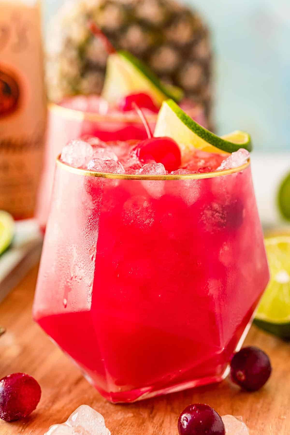 Close up of a bay breeze cocktail garnished with a lime and a cherry.