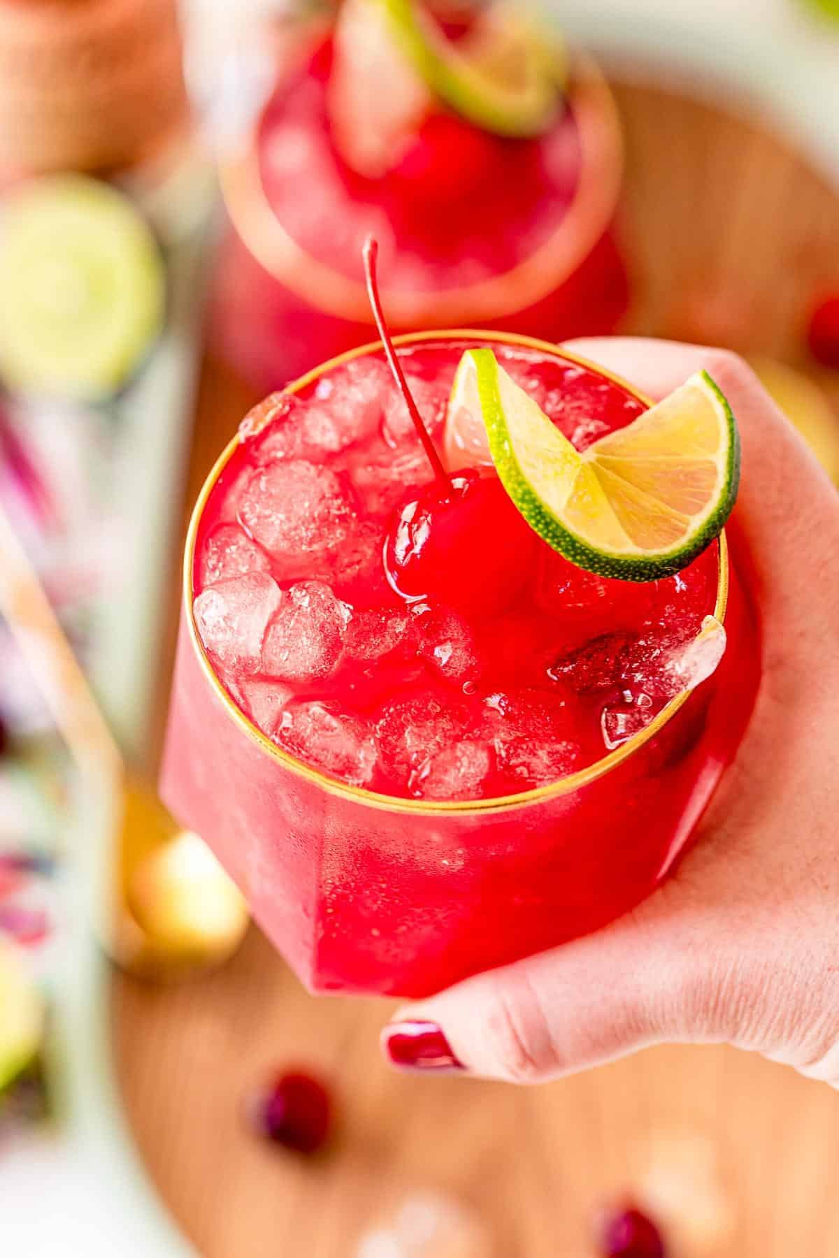 bright red cocktail in a person's hand.