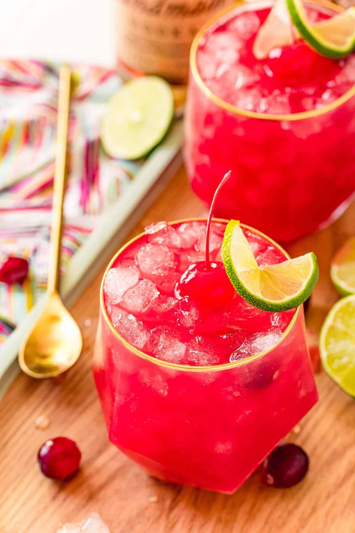 Overhead view of two bright red drinks with ice, a cherry, and a lime.