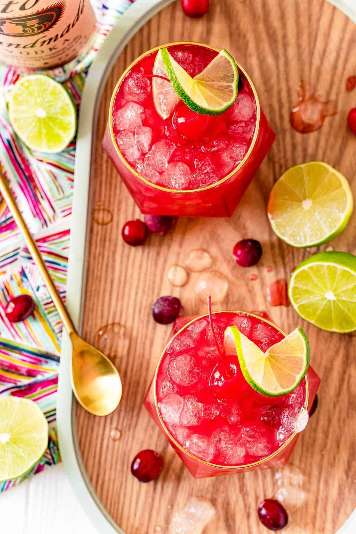 Overhead view of two bright red cocktails served on ice.