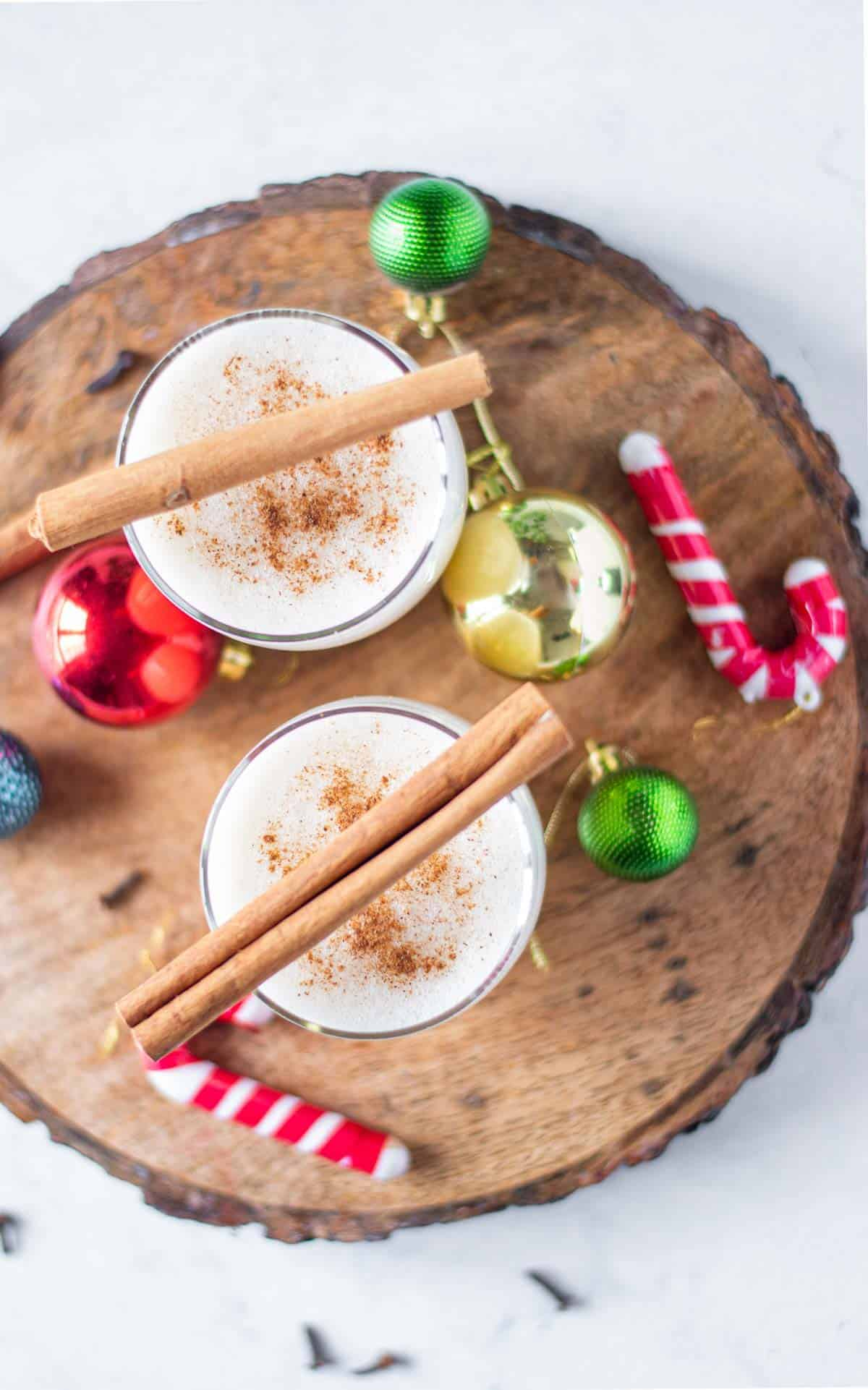 Overhead view of two festive cocktails garnished with cinnamon sticks.