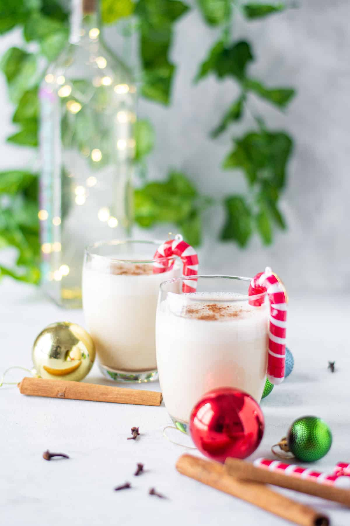 Two cocktails made with egg and milk in a festive holiday scene.