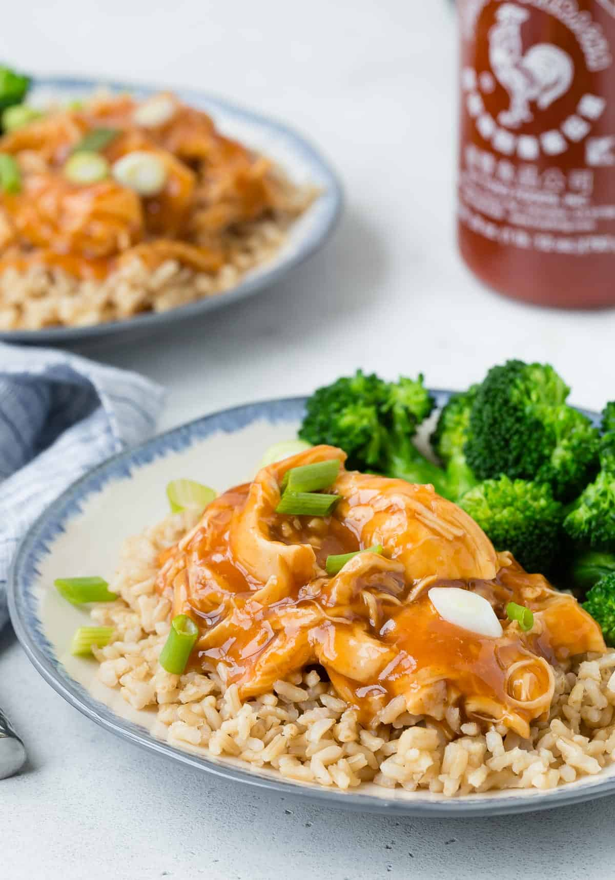 Chicken, rice, and broccoli on a plate with sriracha in the background.