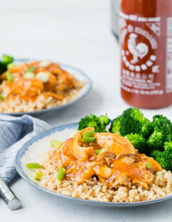Cooked chicken, rice, and broccoli, with a bottle of sriracha in the background.