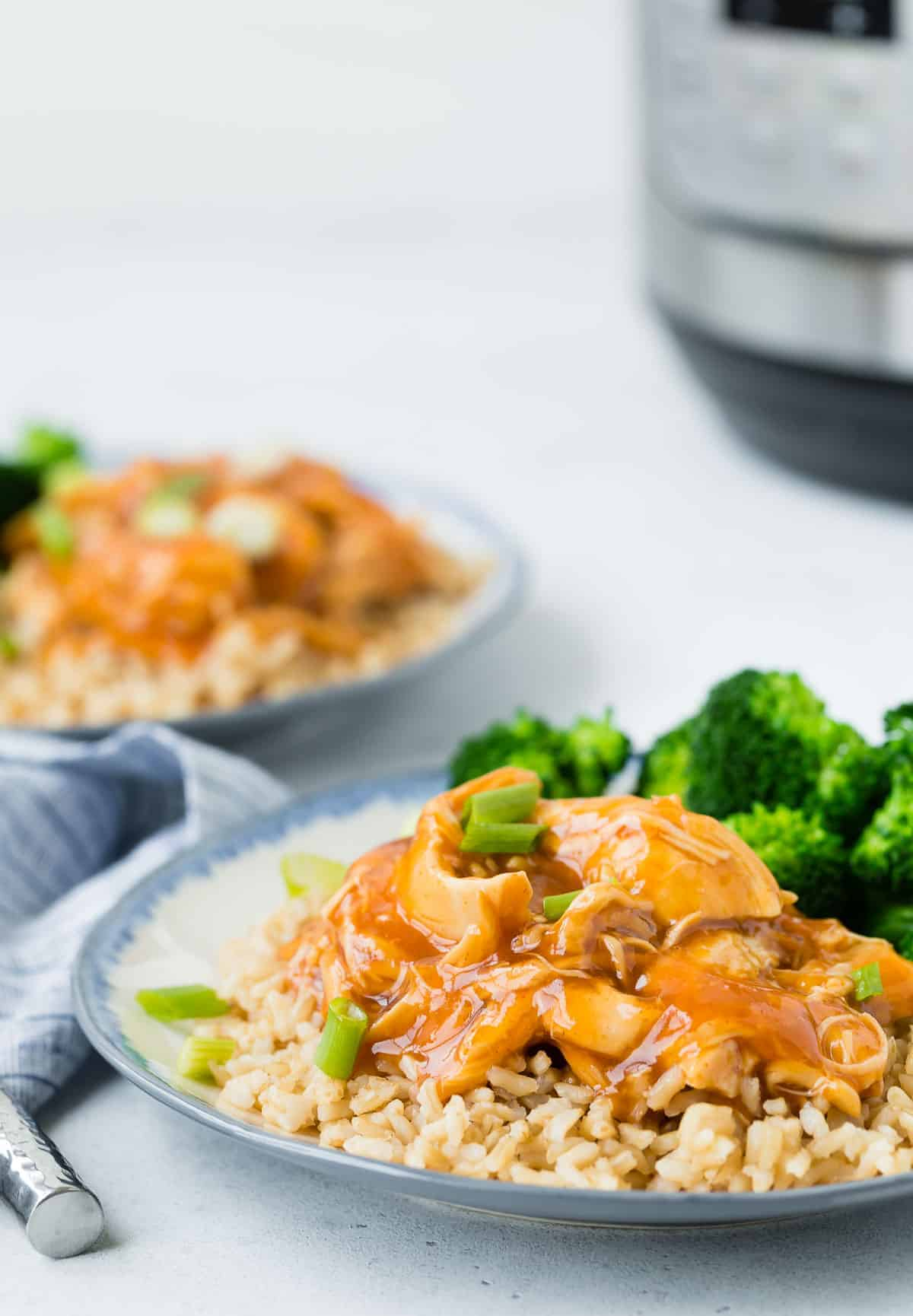Two plates of glazed chicken, rice, and broccoli, with an instant pot in the background.