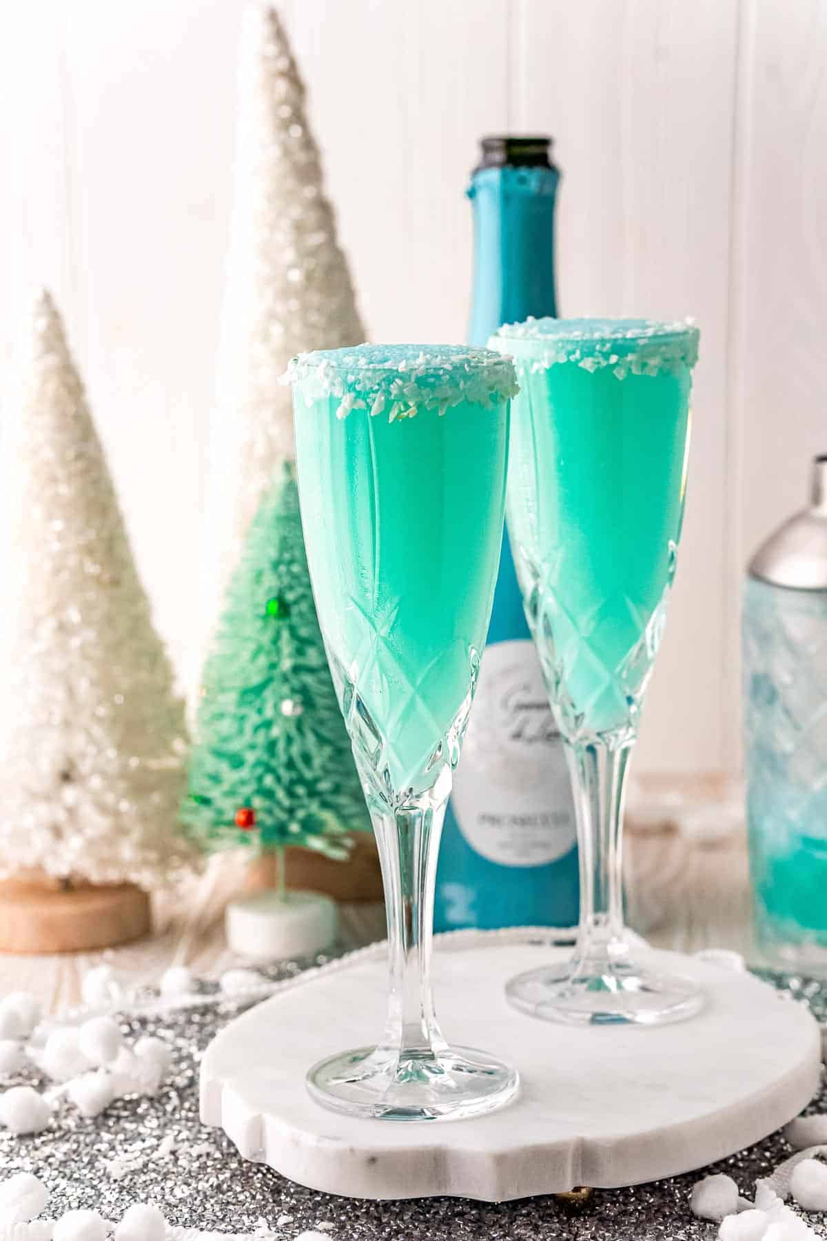 Two bright blue mimosas with a festive winter background.
