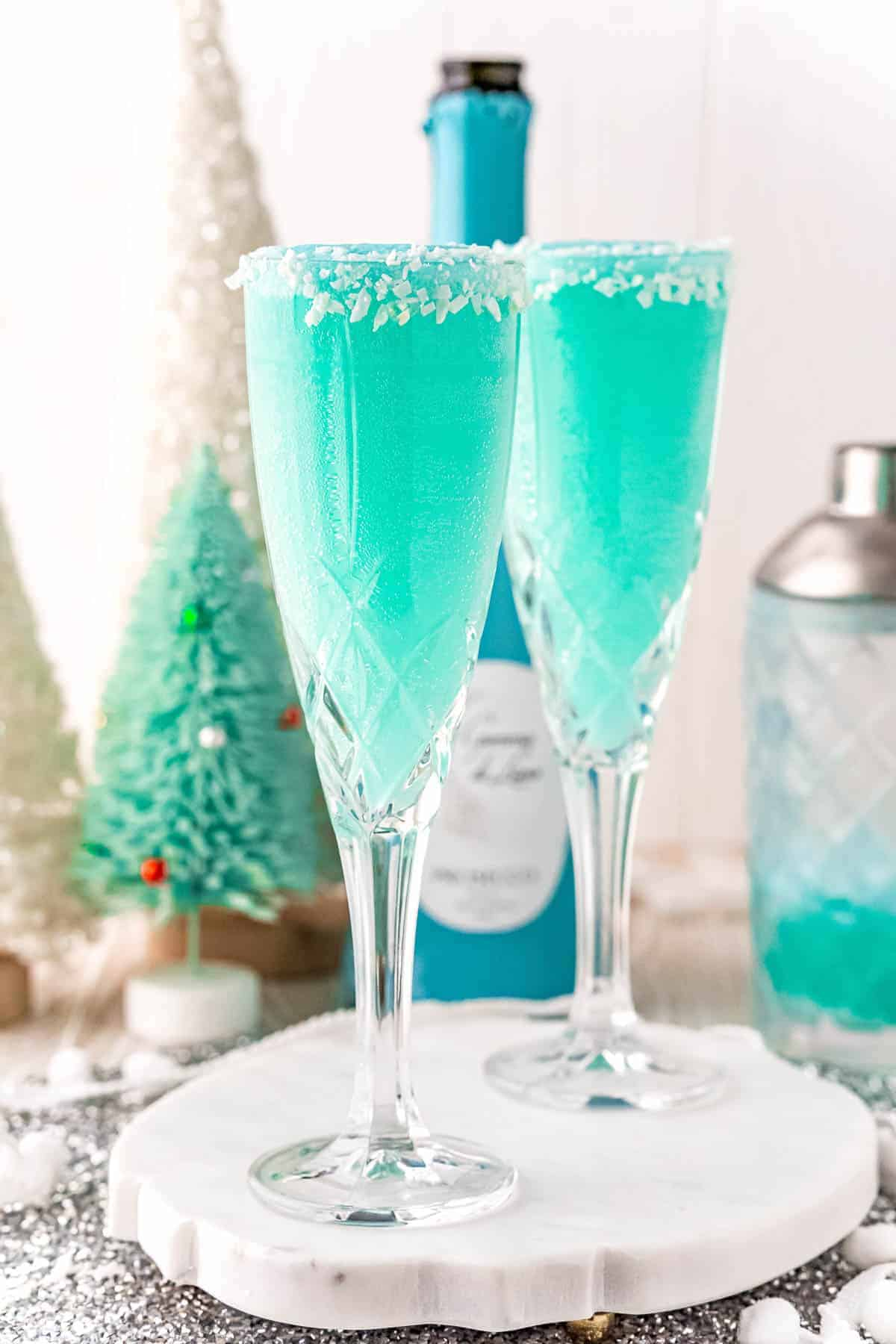 Festive bright blue drink in champagne flutes.