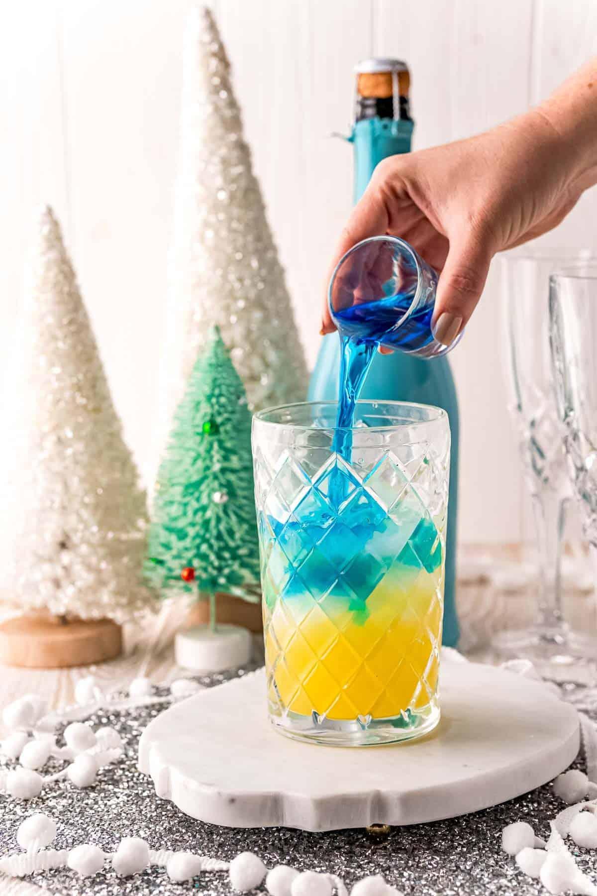 Blue liquid being poured into orange juice.