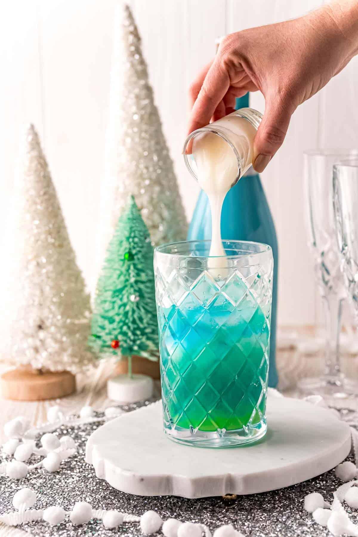 White liquid being poured into blue liquid.