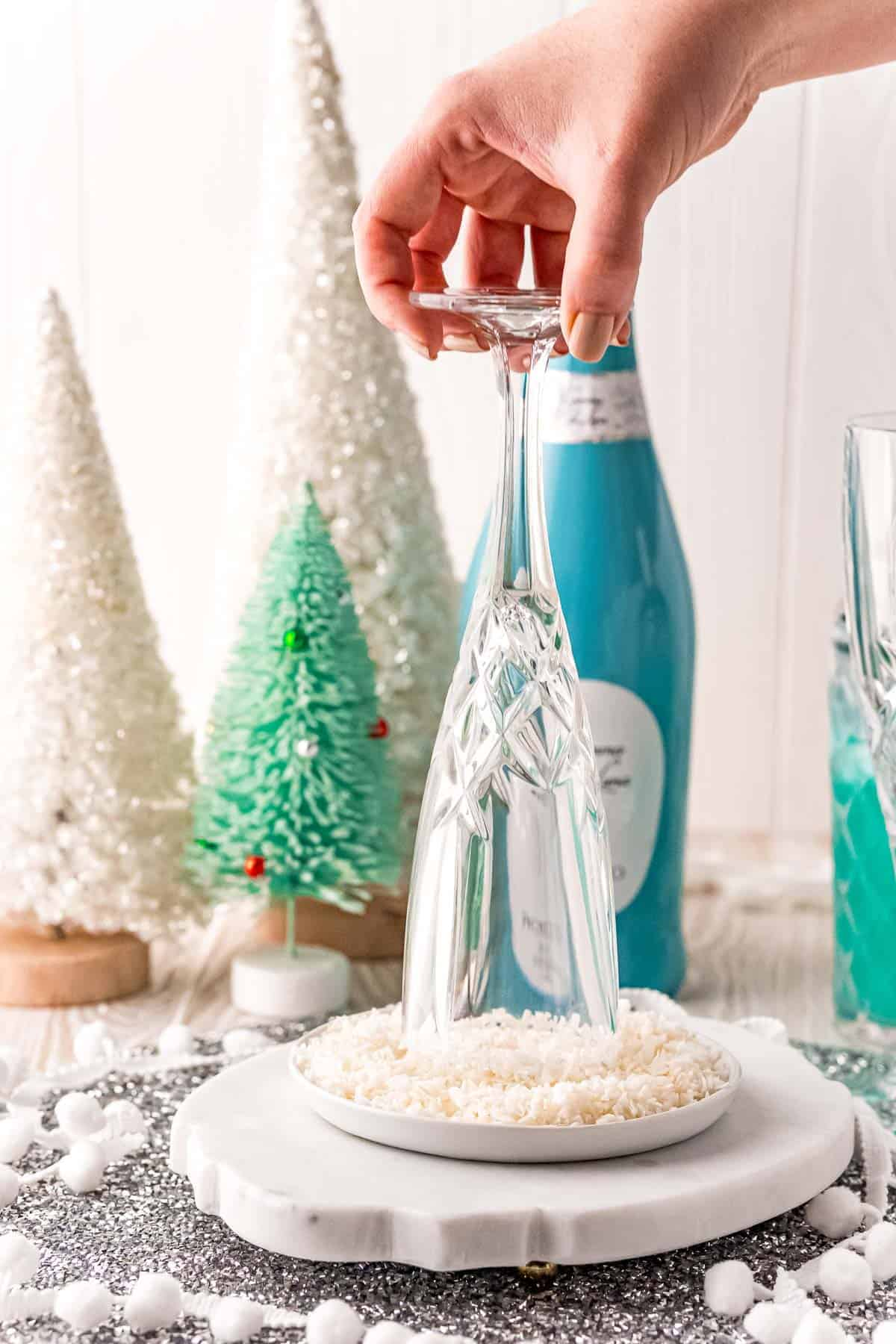 Champagne flute being rimmed with coconut flakes.
