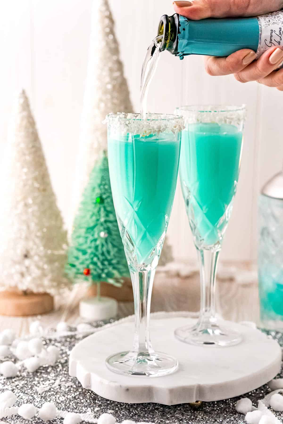 Prosecco being poured into a blue cocktail.