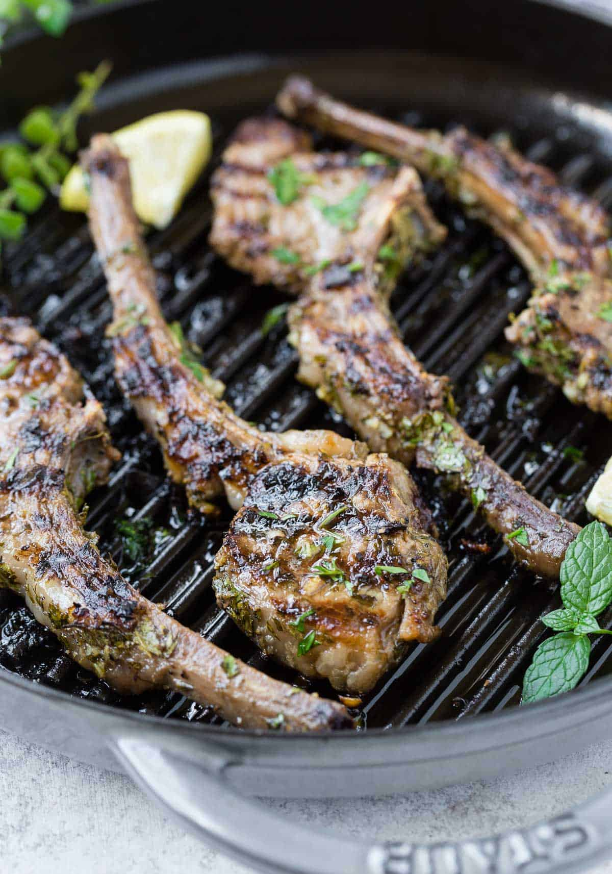 Cooked lamb on a grill pan with fresh herbs and lemon.