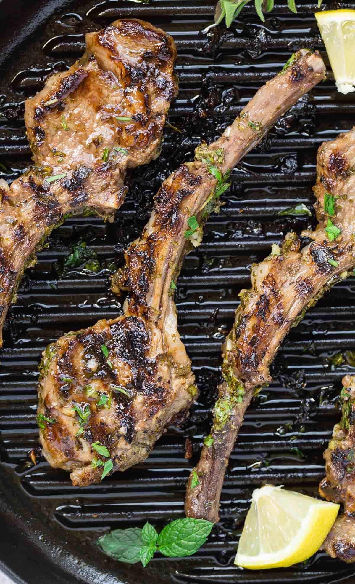 Grilled lamp chops with fresh herbs and lemon wedges.