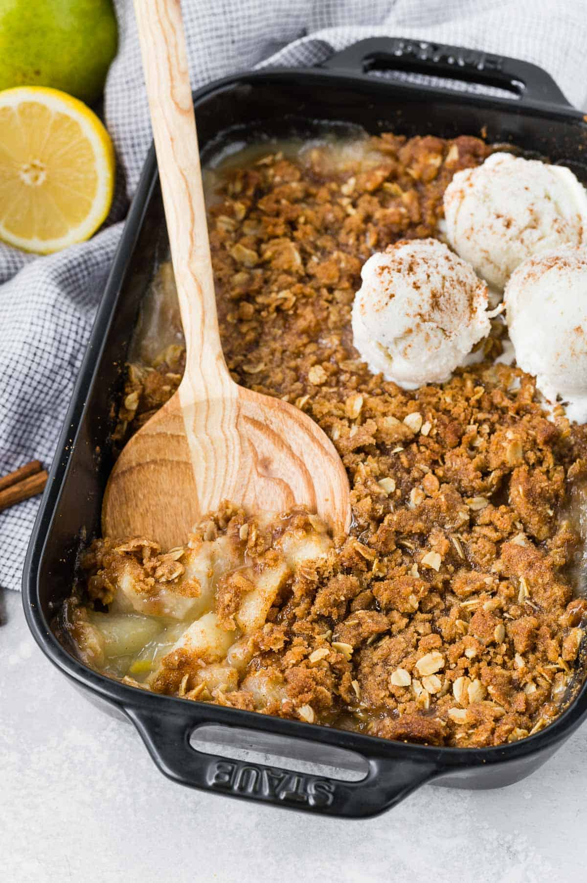 Black baking dish with pear crumble spiced with cinnamon and ginger. Topped with ice cream.