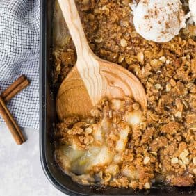 Peach crisp with ginger in a black baking dish, being scooped out with a wooden spoon.