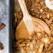 Pear crisp in a black baking dish with a wooden spoon.