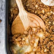 "Crisp in a black baking dish, text overlay reads ""pear crisp with ginger, rachelcooks.com"""