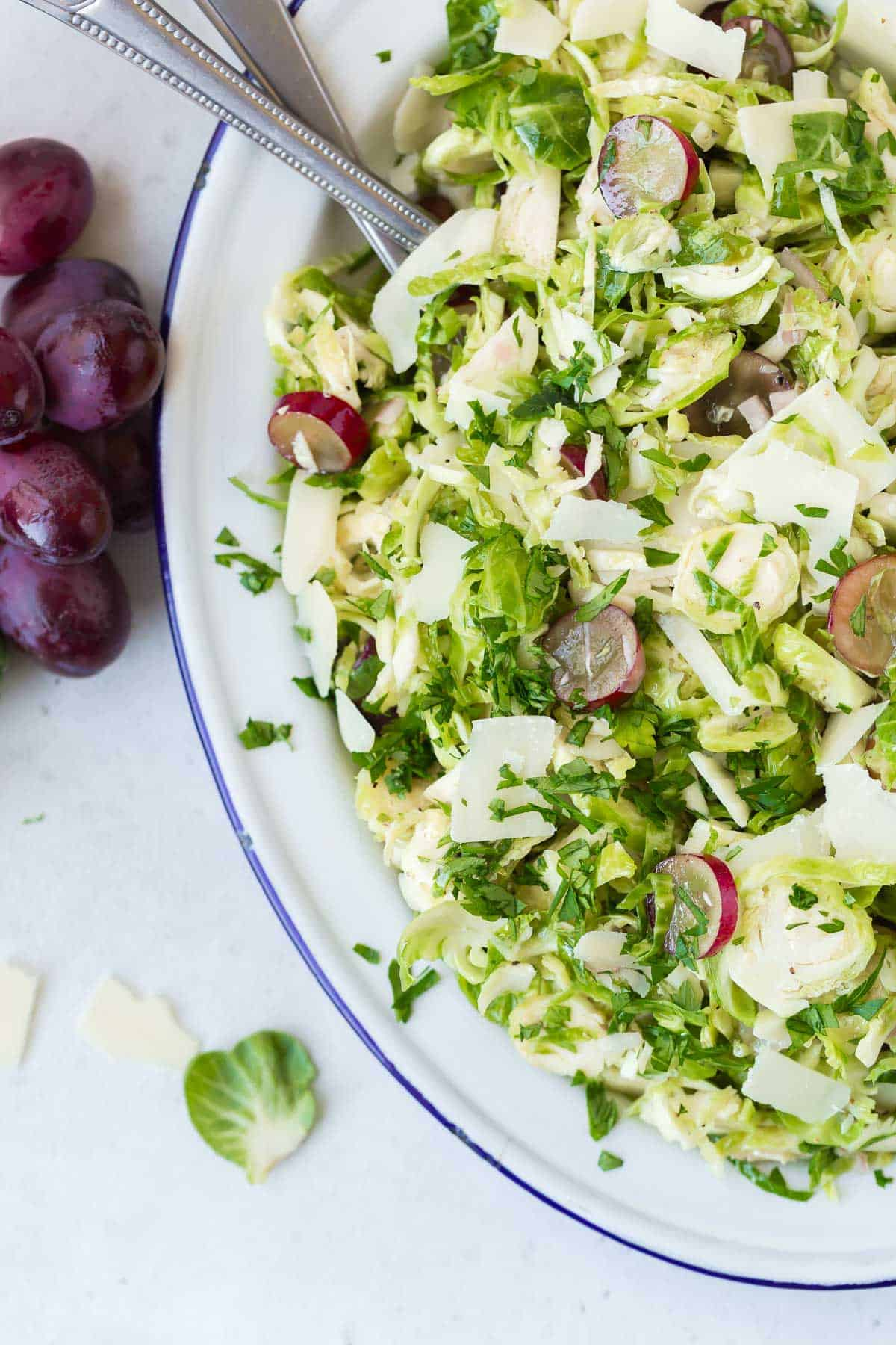 Shaved brussels sprouts salad with grapes, parsley, and parmesan cheese.