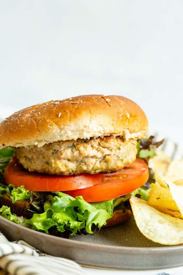 Close up of a turkey burger on a bun with lettuce and tomato.