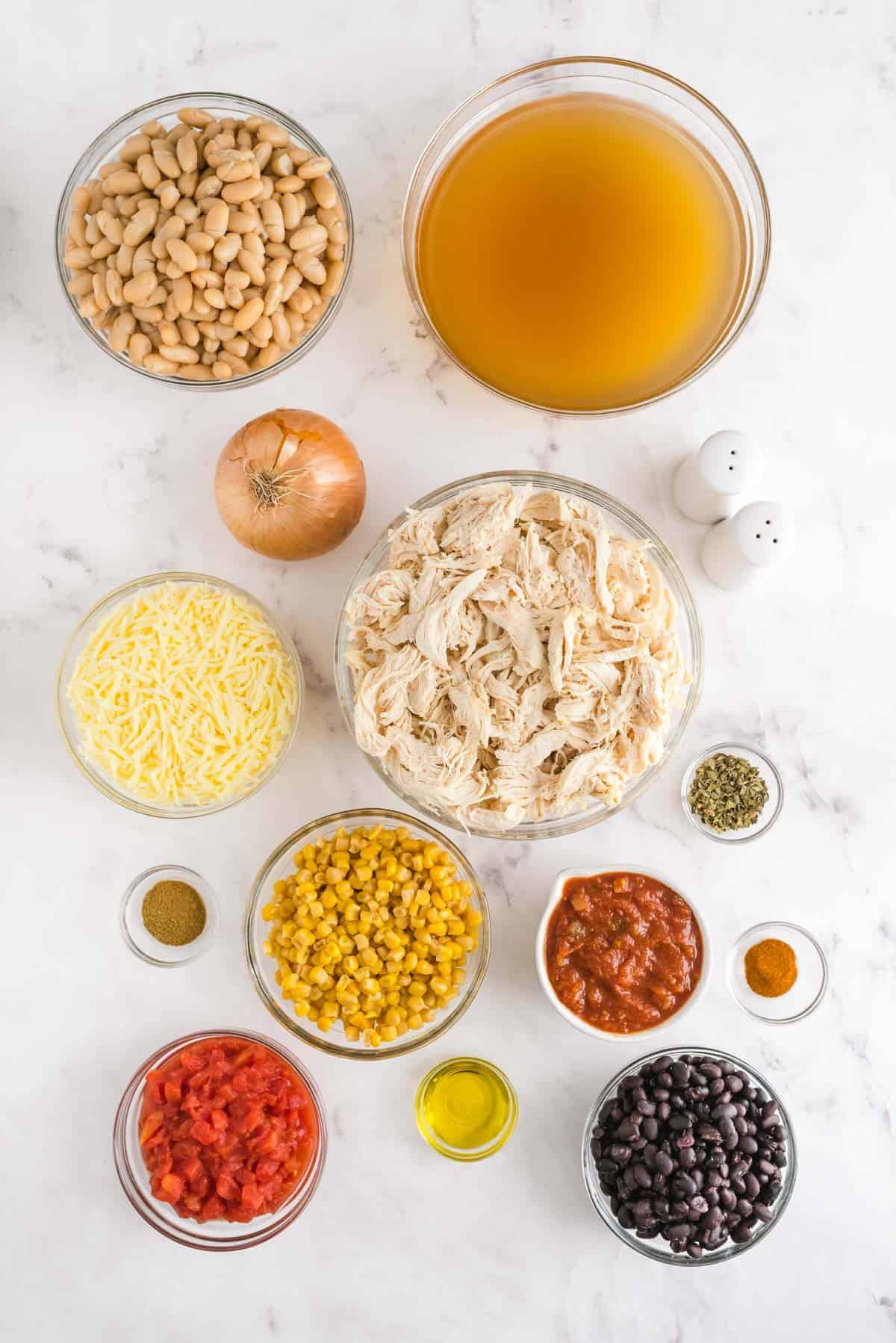 Overhead view of ingredients needed for white chili, all in glass bowls.
