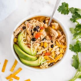 Chicken chili in a bowl garnished with avocado, cilantro, cheese.