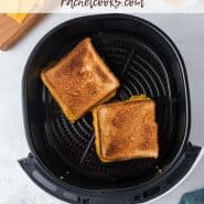 """Two grilled cheese sandwiches in an air fryer basket. Text overlay reads """"air fryer grilled cheese, and recipe ideas!"""""""