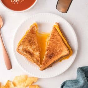 Air fryer grilled cheese sandwich on a white plate, halves pulled apart to show cheese.