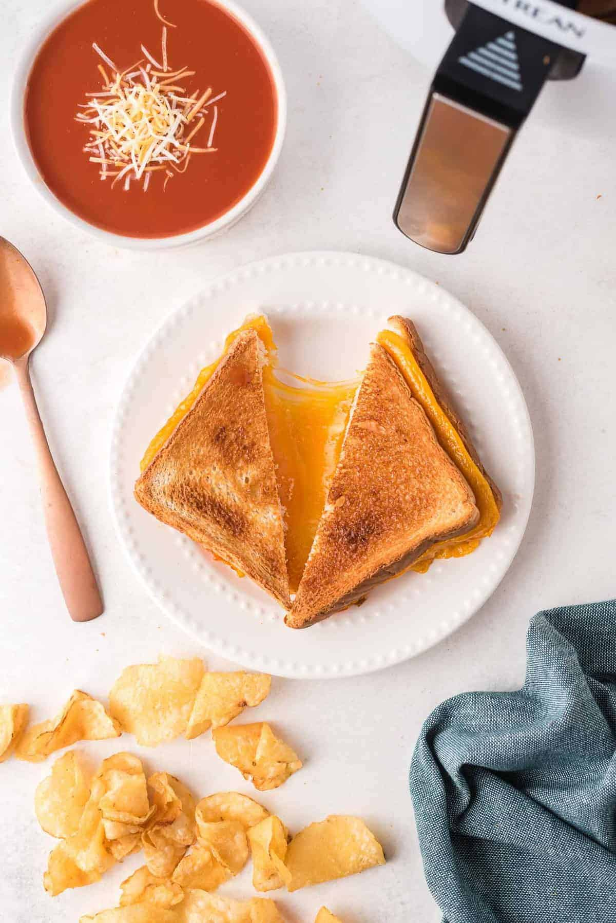 Overhead view of a grilled cheese sandwich on a white plate, being pulled apart to show cheese.