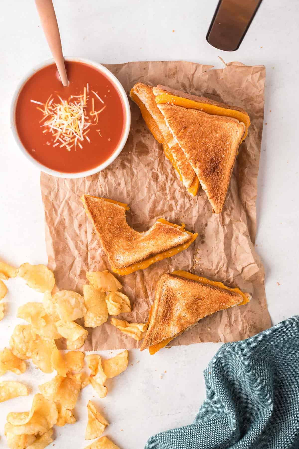 Toasted sandwich with cheese, alongside potato chips and tomato soup.
