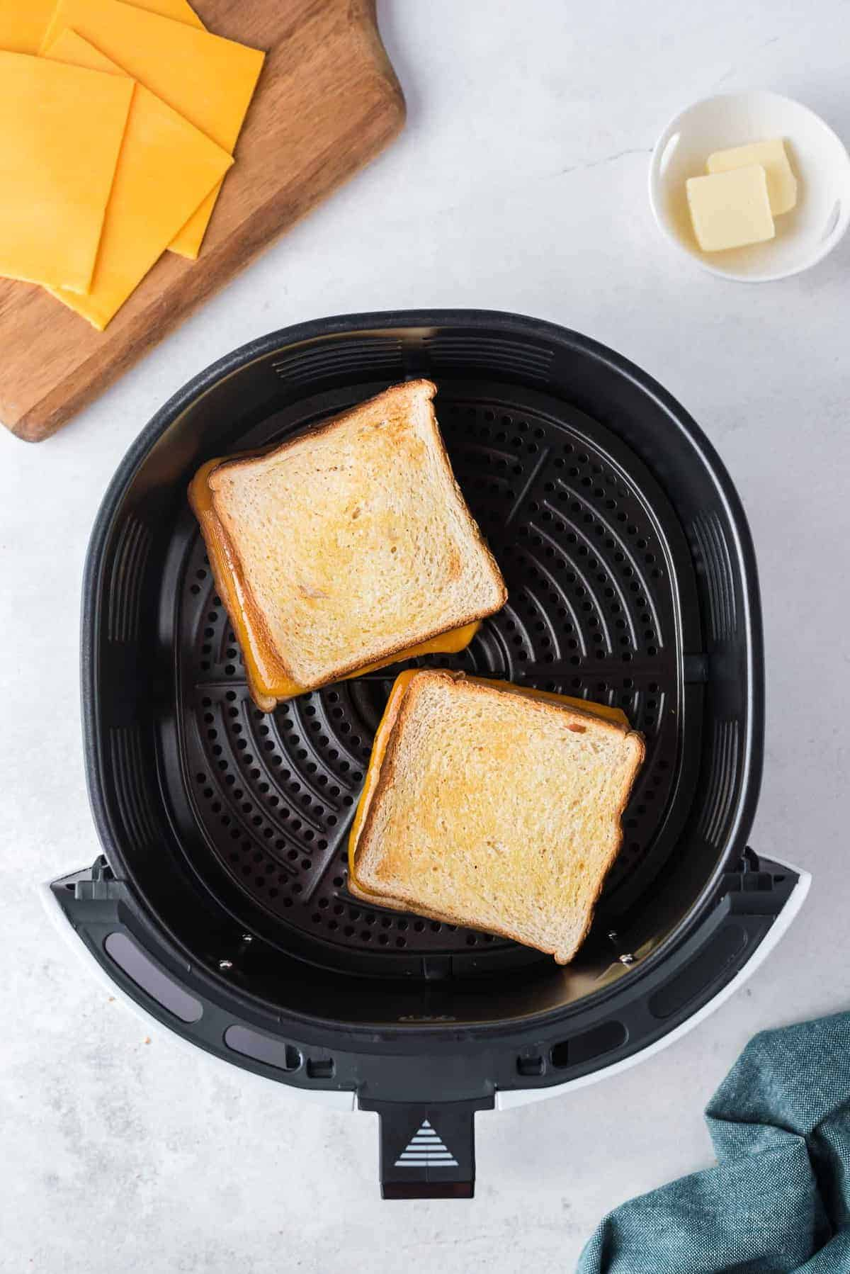 Grilled cheese being made in an air fryer.