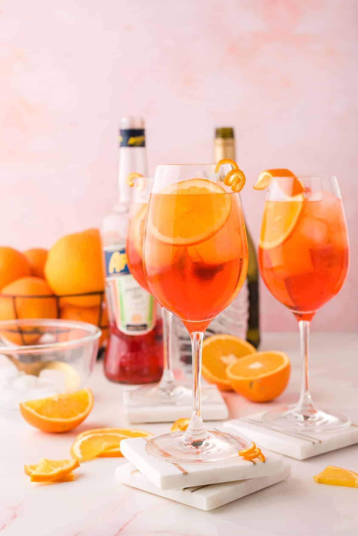 Thre glasses of aperol spritz, with the ingredients need to make it in the background.