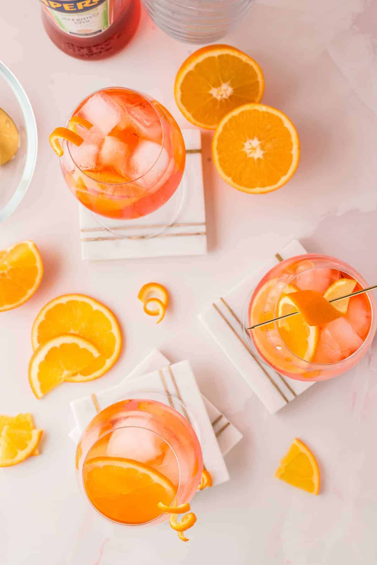 Overhead view of orange-colored drinks over ice, orange slices scattered around.